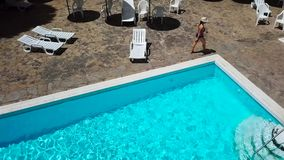 La visión desde el top como mujer en un traje de baño azul toma el sol en un ocioso, se levanta, va a la piscina y nada en la pis