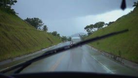 La visión desde la ventanilla del coche en la manera durante la lluvia entre las montañas verdes almacen de video