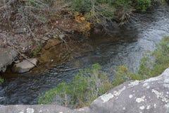 La visión desde las rocas sobre la cama de río muestra un descenso largo abajo imagen de archivo libre de regalías