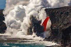 La visión diurna aérea del top de la cascada formó flujo de lava roja del volcán en Hawaii que estallaba en el mar Foto de archivo