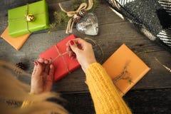 La visión en las mujeres da el adornamiento de la caja del regalo de Navidad con amor en una tabla de madera Fotografía de archivo