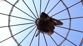 La visión inferior como morenita flexible hace la guita en el aire, la acrobacia aérea metrajes
