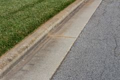 La visi?n pescada con ca?a form? el encintado concreto, la hierba verde y la calle del asfalto imagen de archivo libre de regalías