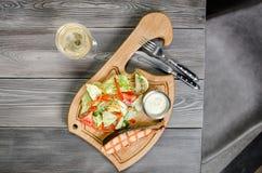 La visión superior asó a la parrilla el filete de color salmón con el vino blanco, salsa de tártaro, verduras frescas servidas en Fotos de archivo