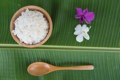 La visión superior cocinó el arroz en cuenco en la cuchara y la orquídea verdes de la hoja del plátano Imagen de archivo libre de regalías
