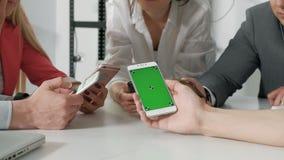 La visión superior da el círculo usando el teléfono en el café - escena interior enviciada móvil multirracial de los amigos desde almacen de video