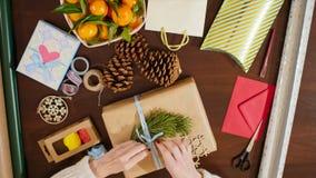 La visión superior en el ` s de la señora da el adornamiento del regalo de Navidad con la cinta y el pino Imagen de archivo libre de regalías