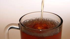 La visión superior, jet del té caliente llena la taza de cristal metrajes