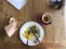 La visión superior que miraba abajo en la tabla acabó la placa y el café adentro bien Foto de archivo