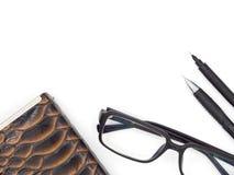La visión superior tiró de plumas, de vidrios y de la cartera en el backgroun blanco Fotografía de archivo