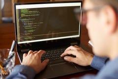 La visión trasera sobre el hombro tiró de programador del desarrollador con el ordenador portátil Código de programa y datos de l fotografía de archivo libre de regalías