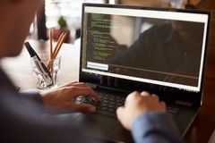 La visión trasera sobre el hombro tiró de programador del desarrollador con el ordenador portátil Código de programa y datos de l fotos de archivo libres de regalías