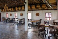 La visión tropical en restaurante, mucho grupo de tablas de madera y las sillas con los barriles de vino adornan en el cuarto imagen de archivo libre de regalías