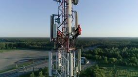 La vista aérea a la antena celular, el amo de radio que trabaja en las telecomunicaciones se eleva vestido en el casco almacen de metraje de vídeo