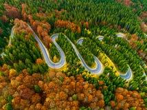 La vista aérea de la carretera con curvas con otoño coloreó el bosque Fotos de archivo