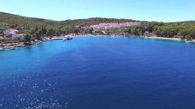 La vista aérea de la bahía azul clara con los apartamentos en la colina y el público varan, Croacia almacen de video