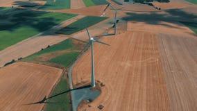 La vista aérea de las turbinas de viento y de los gernerators del viento en el movimiento en un día de veranos sobre trigo cosech almacen de video