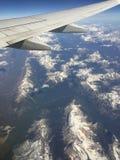 La vista aérea de montañas rocosas y el aeroplano se van volando Imagenes de archivo