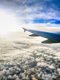 La vista aérea de nubes suaves y el aeroplano se van volando en salida del sol a través de una ventana de los aviones Fotografía de archivo libre de regalías