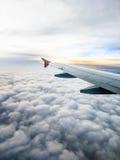 La vista aérea de nubes tempestuosas y el aeroplano se van volando en salida del sol a través de una ventana de los aviones Foto de archivo