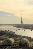 La vista aérea de Riga, la radio del Daugava del río y de Riga y la TV se elevan en la puesta del sol de la iglesia de San Pedro, Imagen de archivo