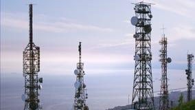 La vista aérea de telecomunicaciones se eleva las antenas y paisaje urbano en el fondo