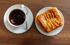 La vista aérea de una taza de café caliente sirvió en una mesa de centro texturizada de madera al lado de una torta de la piña fotografía de archivo libre de regalías