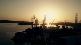 La vista aérea del astillero cranes la silueta en la puesta del sol metrajes