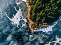 La vista aérea del bosque y del lago congelado de la nieve del invierno desde arriba capturó con un abejón en Finlandia Fotografía de archivo