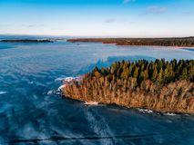La vista aérea del bosque y del lago congelado de la nieve del invierno desde arriba capturó con un abejón en Finlandia Foto de archivo