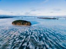 La vista aérea del bosque y del lago congelado de la nieve del invierno desde arriba capturó con un abejón en Finlandia Fotos de archivo libres de regalías