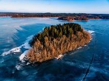 La vista aérea del bosque y del lago congelado de la nieve del invierno desde arriba capturó con un abejón en Finlandia Imagenes de archivo