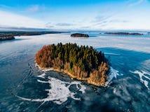 La vista aérea del bosque y del lago congelado de la nieve del invierno desde arriba capturó con un abejón en Finlandia Imágenes de archivo libres de regalías