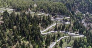 La vista aérea del camino de la serpentina de la montaña con la conducción de los camiones y de automóviles en zigzag entra hacia almacen de metraje de vídeo