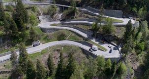 La vista aérea del camino de la serpentina de la montaña con la conducción de los camiones y de automóviles en zigzag entra hacia metrajes