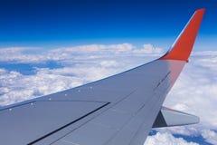 La vista aérea del cielo azul de la nube y el avión se van volando la visión a través de la ventana del aeroplano Imágenes de archivo libres de regalías