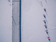 La vista aérea del lago congelado invierno con el embarcadero de madera y las boyas rojas desde arriba capturó con un abejón Fotografía de archivo libre de regalías