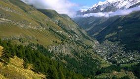 La vista aérea del pueblo de Zermatt, de laderas herbosas con los prados, del canto de la montaña y de la alta nieve capsuló las  almacen de metraje de vídeo