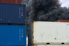 La vista abstracta de los contenedores con columnas de humo tóxico de un fuego industrial se alza en el cielo imagenes de archivo