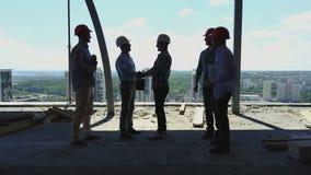 La vista aerea dei costruttori team la stretta di mano con il datore di lavoro dell'uomo di affari sul cantiere, riunione del gru stock footage