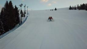 La vista aerea del fuco di un groomer della neve poichè scala la montagna per la preparazione dello sci pende stock footage
