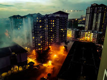 La vista aerea della scena drammatica sotto cui ha assomigliato alle costruzioni è su fuoco dovuto le luci riflesse sulla sera ne Fotografia Stock Libera da Diritti