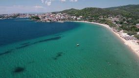 La vista aerea di bella spiaggia con le colline e un villaggio turistico, Neos Marmaras Halkidiki Grecia, si muove in avanti in f video d archivio