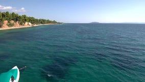 La vista aerea di piccola navigazione gonfiabile della barca al mare in Halkidiki Grecia, si muove in avanti in fuco stock footage