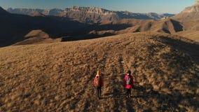 La vista aerea di un viaggiatore di due ragazze con gli zainhi e le macchine fotografiche passeggiano attraverso le colline fra l stock footage
