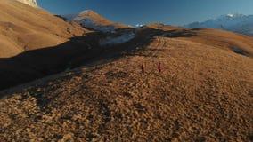 La vista aerea di un viaggiatore di due ragazze con gli zainhi e le macchine fotografiche passeggiano attraverso le colline fra l video d archivio