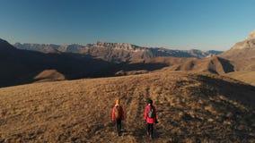 La vista aerea di un viaggiatore di due ragazze con gli zainhi e le macchine fotografiche passeggiano attraverso le colline fra l archivi video