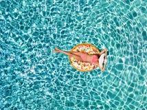 La vista aerea di una ragazza attraente che galleggia sopra il turchese innaffia su un galleggiante a forma di ciambella immagini stock libere da diritti