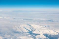 La vista aerea sulla neve ha ricoperto i alpes dal cielo blu dell'aeroplano e Fotografia Stock Libera da Diritti