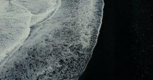 La vista aerea superiore di grande onda si solleva sulla riva della spiaggia vulcanica nera in Islanda stock footage